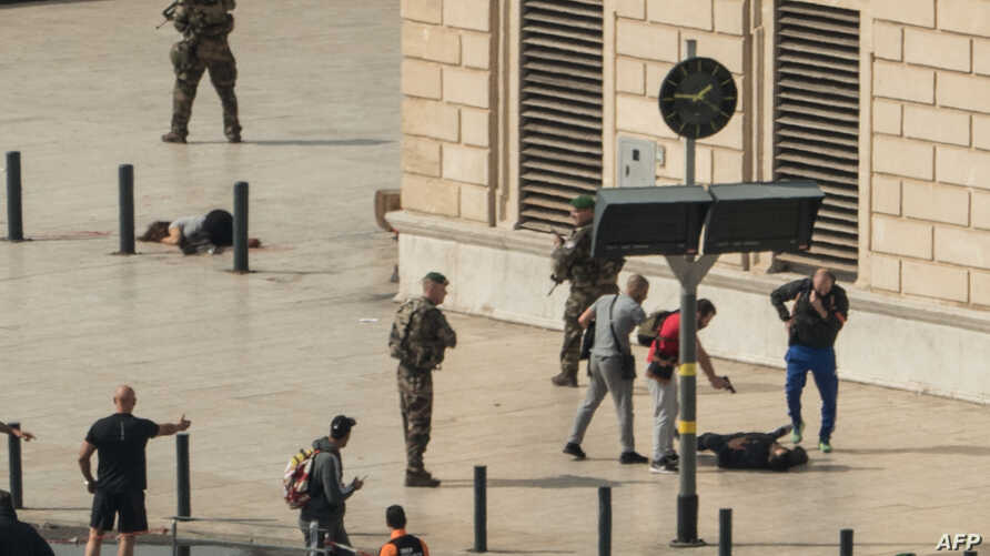 French police point a gun at a man on the ground (C) as a stabbed woman lies (L) while soldiers secure the area following an attack on October 1, 2017 at the Saint-Charles main train station in the French Mediterranean city of Marseille.