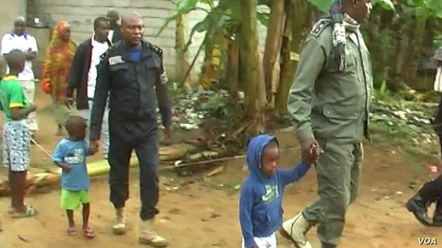Police officers lead away children after the search of a suspect's home in Kiossi, Cameroon, March 3, 2018. (M. Kindzeka/VOA)