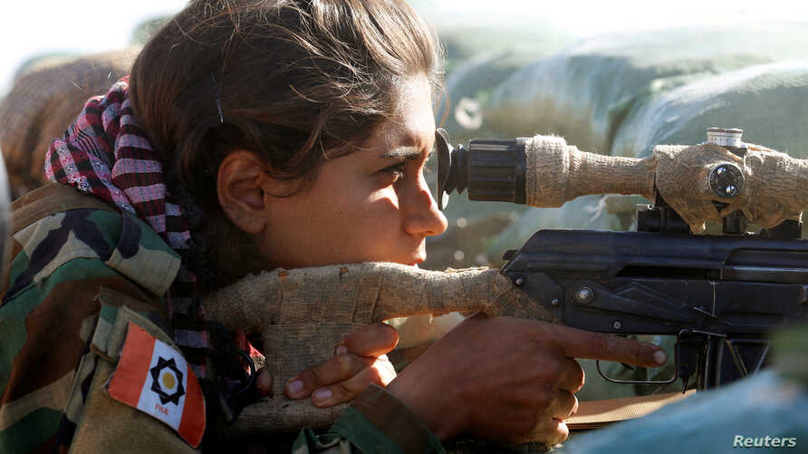An Iranian-Kurdish female fighter aims with her weapon during a battle with Islamic State militants in Bashiqa, near Mosul, Iraq, Nov. 3, 2016.