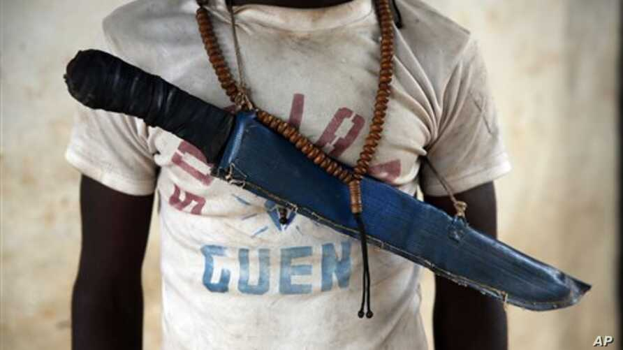 In this April 15, 2014 photo, an Anti-Balaka Christian fighter stands on the front of a looted Muslim store in Guen, some 250 kilometers north of Bangui, Central African Republic. As U.N. peacekeepers prepare to go into the Central African Republic t