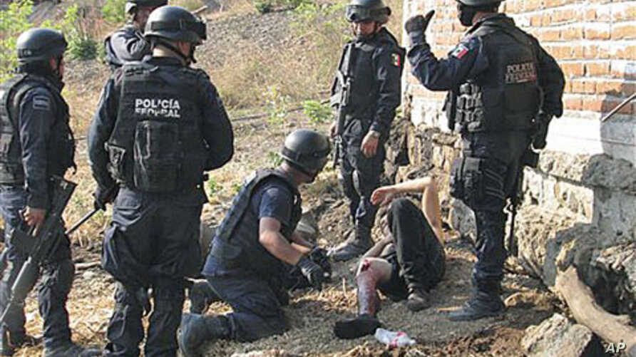 Federal police officers stand over an injured man, allegedly belonging to the La Familia Michoacana drug cartel, after a gun battle was held a day earlier in Jilotlan, Mexico, May 28, 2011 (file photo)