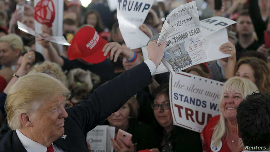 """U.S. Republican presidential candidate Donald Trump holds up a newspaper with a headline reading """"Clinton, Trump Lead"""" at a campaign rally in Warwick, Rhode Island, April 25, 2016."""