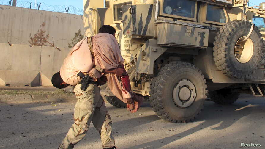 FILE - An Afghan security personnel carries a wounded man after a suicide car bomb blast attacked a military convoy in Lashkar Gah, Helmand province, Afghanistan, Nov. 15, 2015.