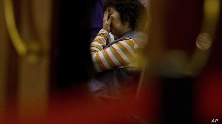 A relative of Chinese passengers aboard the missing Malaysia Airlines Flight MH370 waits for a briefing at a hotel ballroom in Beijing, March 18, 2014.
