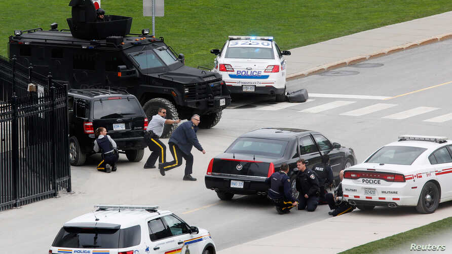 Police officers take cover near Parliament Hill following a shooting incident in Ottawa, October 22, 2014.