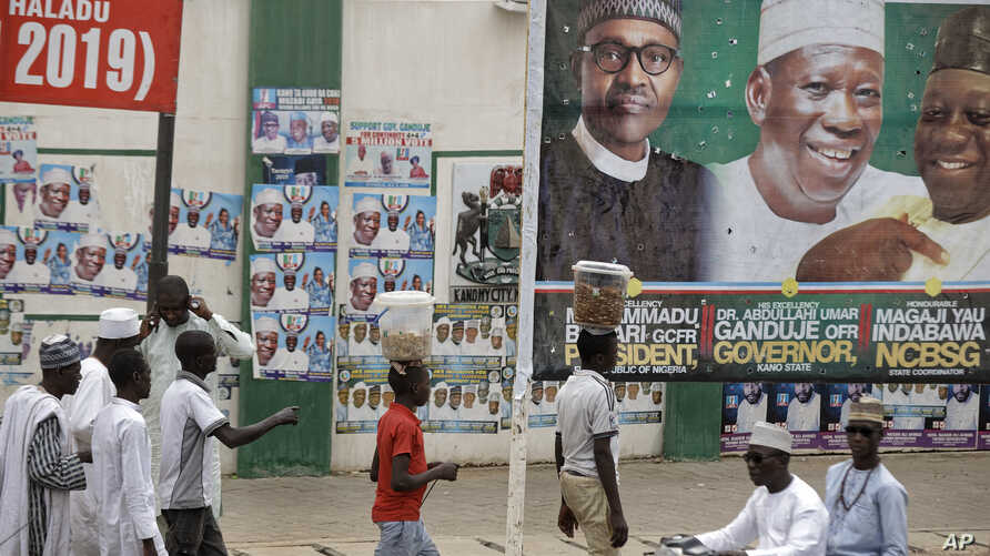 Street-vendors and others walk past a billboard showing Nigeria's President Muhammadu Buhari and other party officials, in Kano, northern Nigeria, Feb. 26, 2019. Buhari's election lead grew on Tuesday.