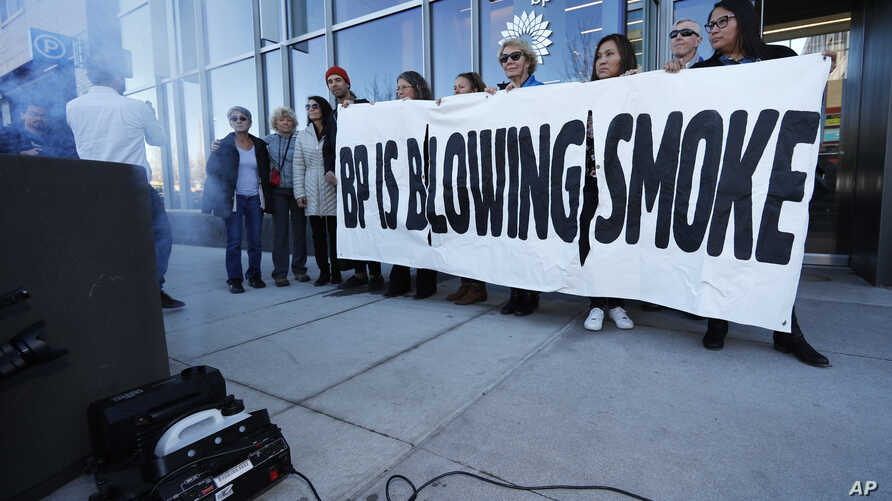 Activists from ProgressNow Colorado, grassroots organizations and stakeholders join forces to demonstrate outside the United States headquarters of BP, Nov. 14, 2018, in Denver.