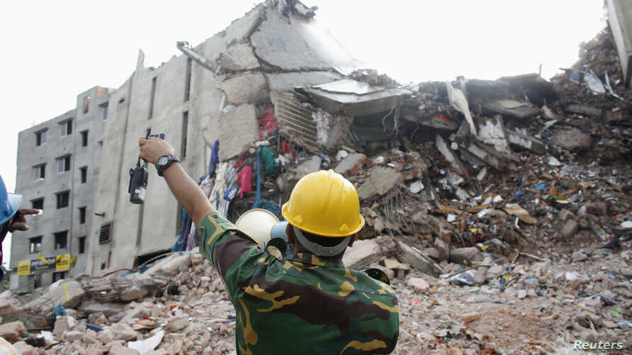 A rescue worker attempts to find survivors from the rubble of the collapsed Rana Plaza building in Savar, 30 km (19 miles) outside Dhaka, April 30, 2013.