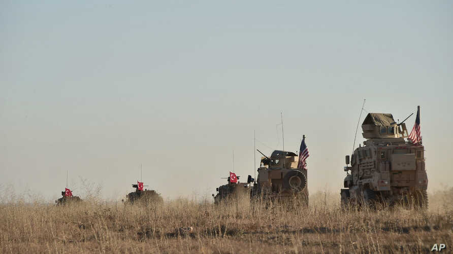 In this photo taken Nov. 1, 2018, Turkish and U.S. troops conduct joint patrols around the Syrian town of Manbij, as part of an agreement that aimed to ease tensions between the two NATO allies