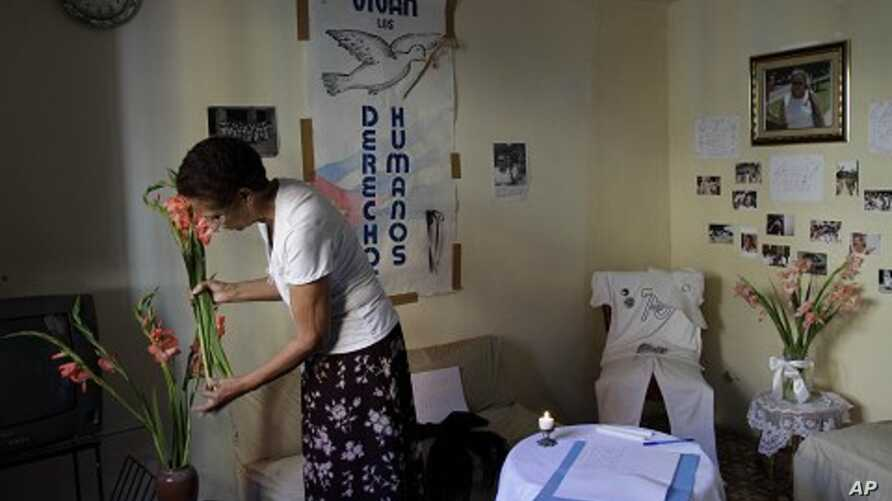 Ramona Rivero, of the Cuban dissident group Ladies in White, places flowers in a vase near a condolence book for the late dissident Wilman Villar in Havana, Cuba, Friday, Jan. 20, 2012.