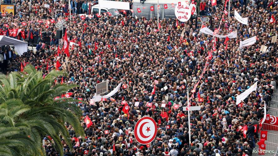 People carry flags as they protest the government's refusal to raise wages in Tunis, Tunisia, Nov. 22, 2018. The country's biggest union called a nationwide strike Thursday in protest.