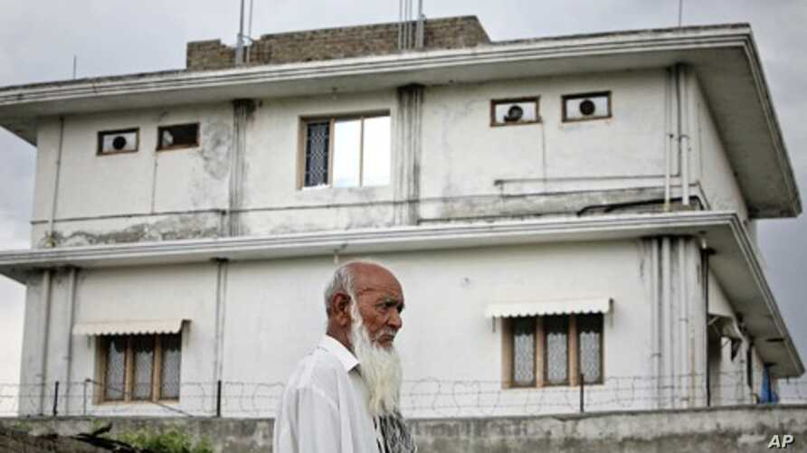 A resident walks on May 5, 2011 past the compound in Abbottabad, Pakistan, where US Navy SEALs killed Osama bin Laden