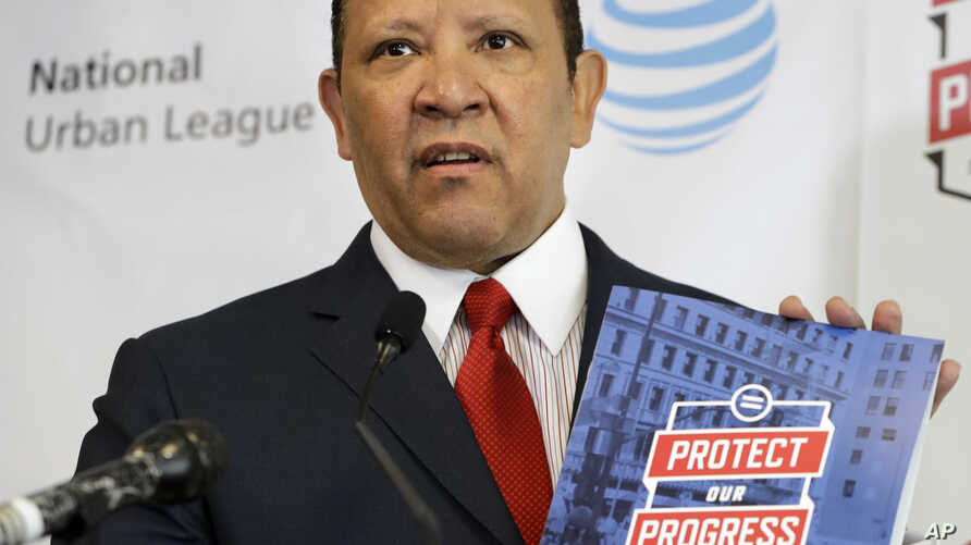 National Urban League President and CEO Marc Morial holds up a copy of the 2017 State of Black America report, May 2, 2017, at the National Urban League in Washington.