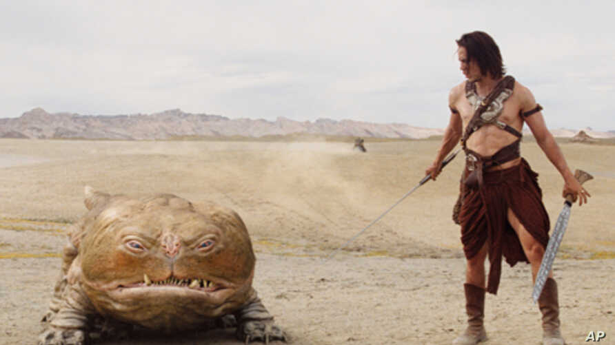 """Taylor Kitsch as the title character in """"John Carter,"""" along with Woola, on Mars."""