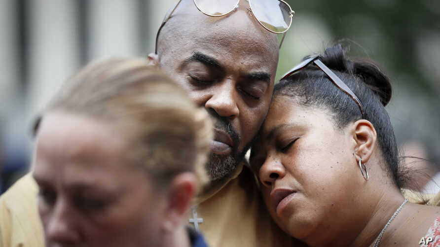 Mourners attend a vigil in Fountain Square where a shooting took place the previous day that claimed the lives of three civilians, Sept. 7, 2018, in Cincinnati. Suspect Omar Enrique Santa Perez entered the Fifth Third Center and began firing before b