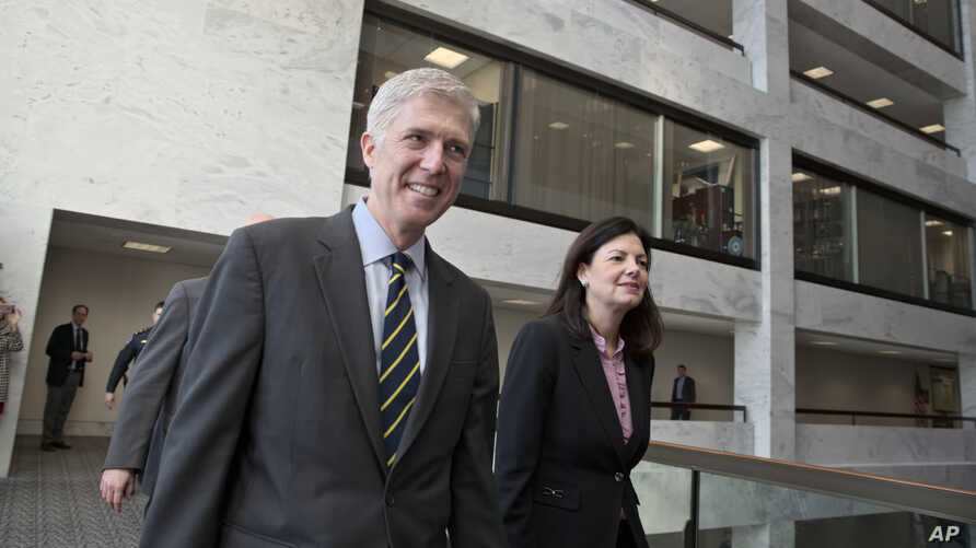 Supreme Court Justice nominee Neil Gorsuch, escorted by former New Hampshire Sen. Kelly Ayotte, arrives for a closed-door meeting with Sen. Jon Tester, D-Mont., at his office on Capitol Hill in Washington, Feb. 6, 2017.