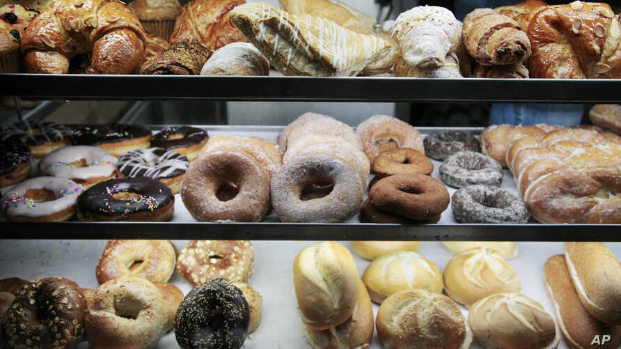 FILE - A selection of pastries, including doughnuts, bagels, rolls, croissants, turnovers and sticky buns are displayed in a New York coffee cart. In studies of mice fed fatty, Western-style diets putting them at risk for heart disease, researchers s