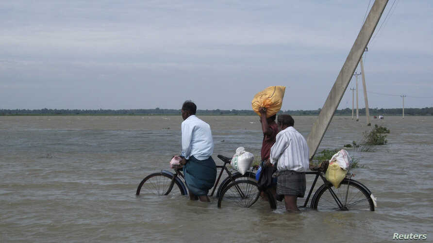 FILE - Sri Lankan men push their bicycles through flood waters after heavy rains in Batticaloa, about 320 km (199 miles) east of Colombo, Jan. 13, 2011.