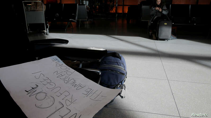 A sign welcoming refugees lies on bench in the international arrivals area of Logan Airport after US President Donald Trump's executive order travel ban in Boston, Massachusetts, US Jan. 30, 2017.