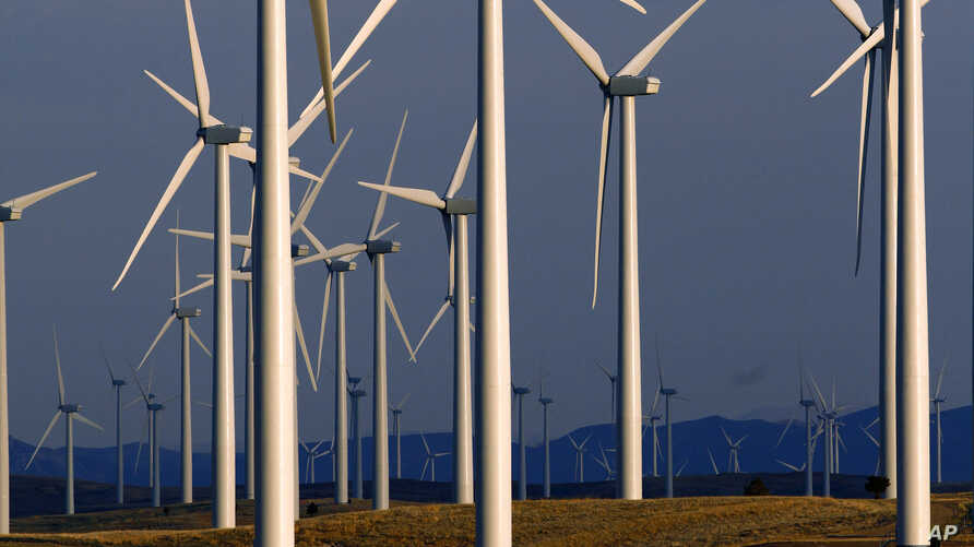 FILE - A wind turbine farm owned by PacifiCorp near Glenrock, Wyoming, cranks out electricity, May 6, 2013.