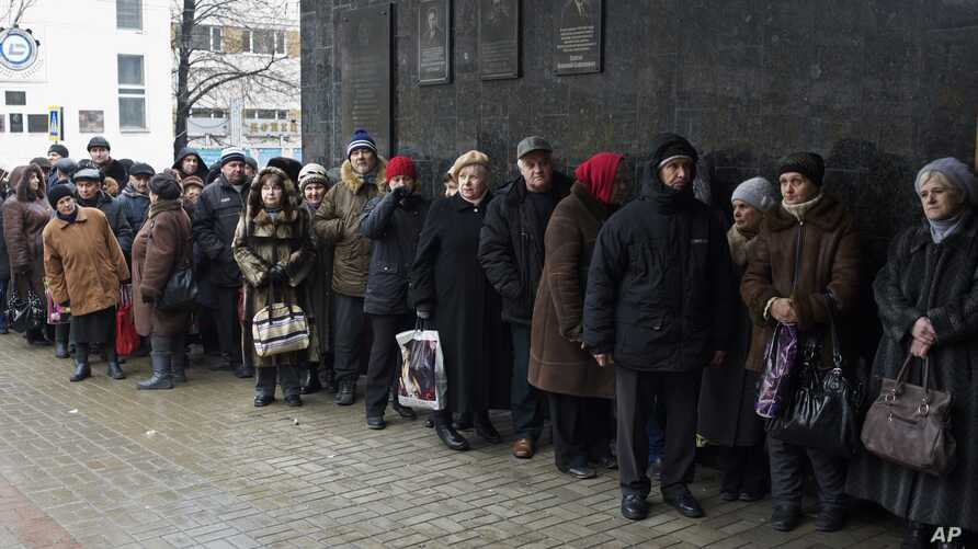 Pensioners stand in a queue to get a financial aid at one of the government offices of the self-proclaimed Donetsk People's Republic in Donetsk, eastern Ukraine, Dec. 12, 2014.