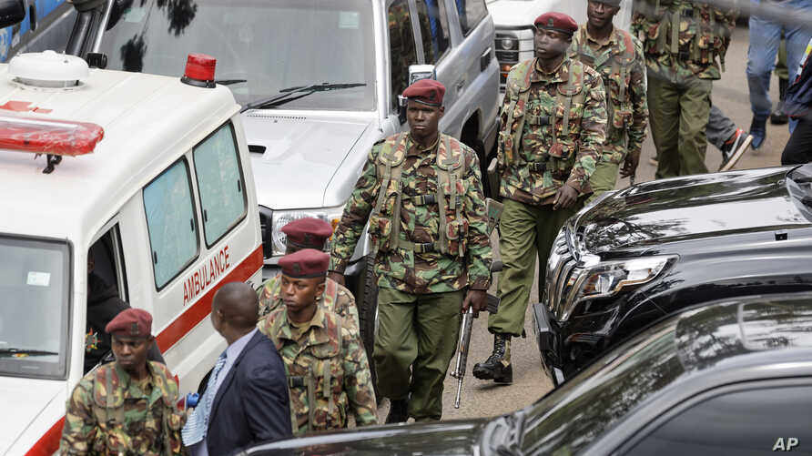 Kenyan security forces walk away from the hotel complex at the scene of the attack in Nairobi, Kenya, Jan. 16, 2019.