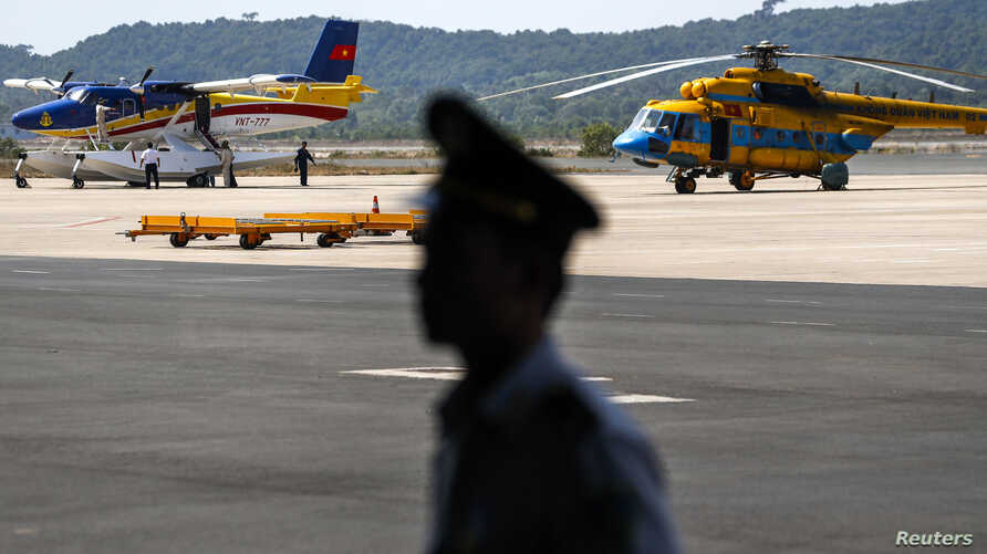 An officer stands guard near Vietnam aircraft before a mission to find the Malaysia Airlines flight MH370 that disappeared from radar screens Saturday, at Phu Quoc Airport on Phu Quoc Island, March 10, 2014.