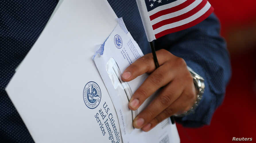 FILE - A newly naturalized U.S. citizen leaves a swearing in ceremony in Los Angeles, U.S., July 18, 2017.