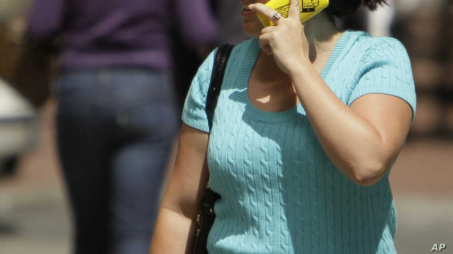 FILE - A woman talks on her cellphone while walking along First Street in San Francisco. NTP scientists and the U.S. Food and DrugAdministration say current safety limits oncellphone radiation are protective.