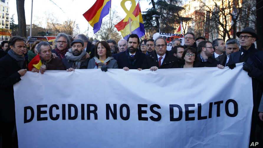 """The president of Catalonian Parliament, Roger Torrent, center, and the Catalan regional President Quim Torra, center right, hold a placard that reads in Spanish: """" To Choose is not a Crime"""", outside the Spanish Supreme Court in Madrid, Tuesday, Feb."""