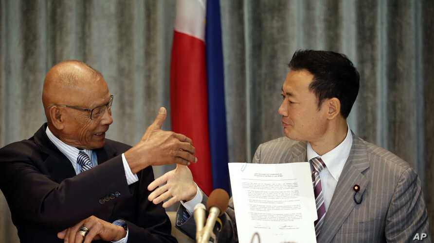 Philippine Congressman Rodolfo Biazon, left, Chair of the House Committee on National Defense, and Hiroshi Nakada, Head of delegation of the Japanese opposition Party for Future Generations, shake hands shortly after signing a non-binding documents t