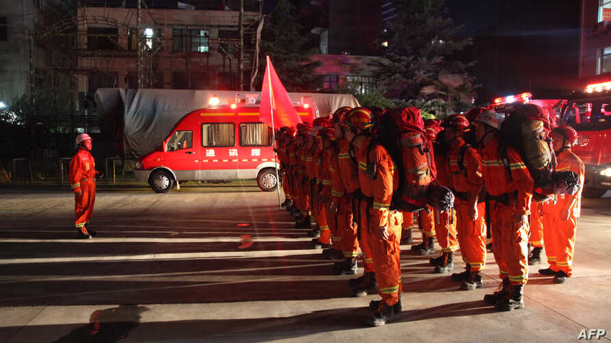 Firefighters stand to attention in Longnan, in China's Gansu province on Aug. 8, 2017, as they prepare to head to Wenxian county after an earthquake centered in neighboring Sichuan province.