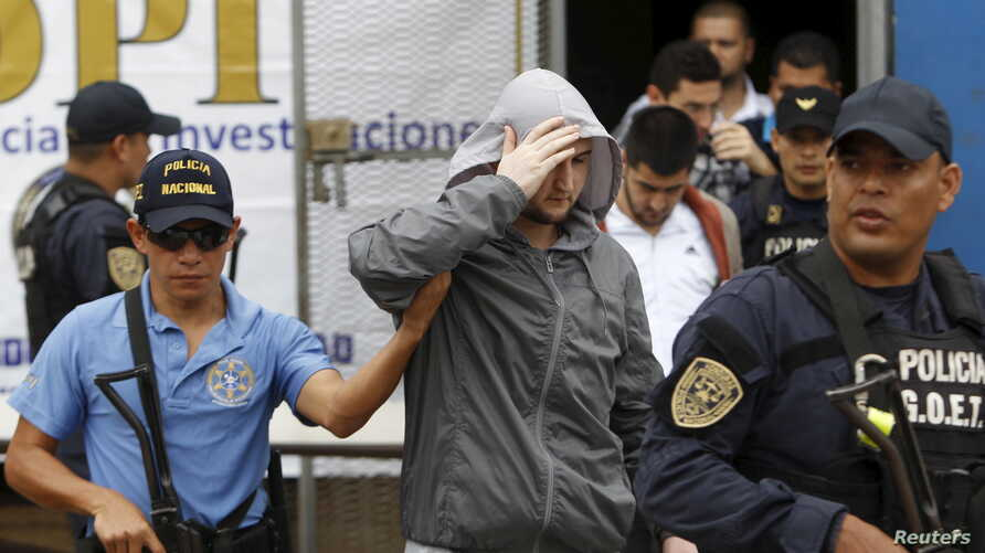 Police in Tegucicalpa escort one of five Syrians ordered jailed after they were found to have used stolen Greek passports to enter Honduras, Nov. 20, 2015.