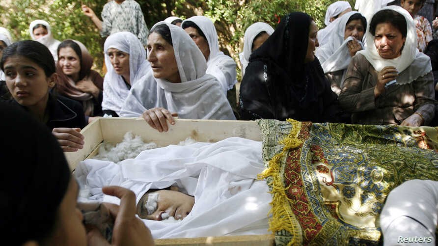 FILE - Relatives of slain Afghan journalist Zakia Zaki, 35, mourn her death, Parwan province, June 6, 2007.