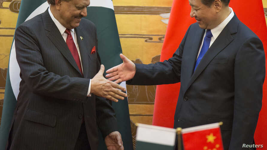 FILE - Pakistan's President Mamnoon Hussain (L) shakes hands with China's President Xi Jinping during a signing ceremony at the Great Hall of the People in Beijing.