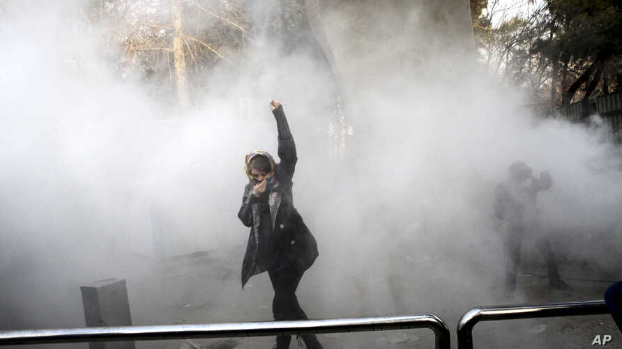 FILE - In this Dec. 30, 2017 file photo taken by an individual not employed by the Associated Press and obtained by the AP outside Iran, a university student attends a protest inside Tehran University.