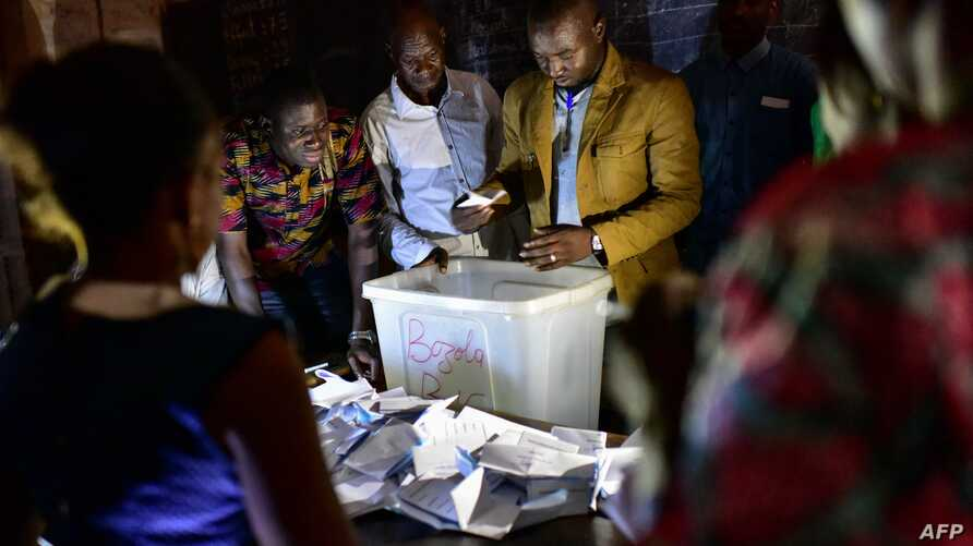 Electoral officials count ballot papers at the polling station on July 29, 2018 in Bamako, during Malian presidential elections.