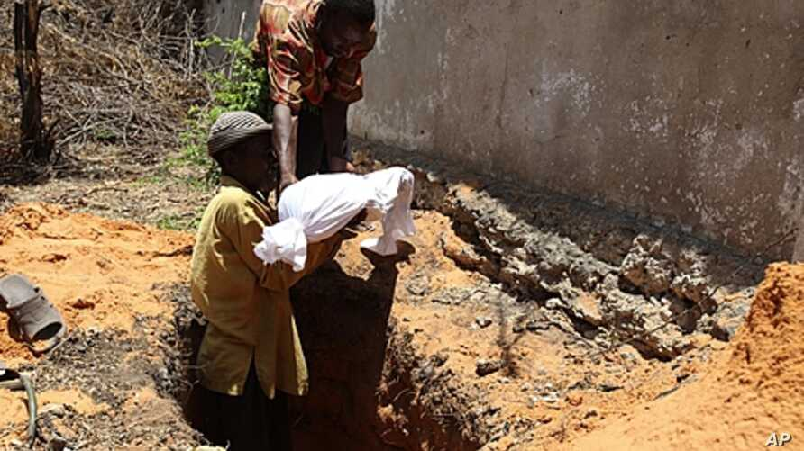 Internally displaced Somali men bury the body of a child who died of malnourishment in Hodan district, south of Mogadishu, Sept. 20, 2011.