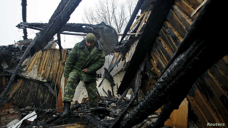 FILE - A Russian member of the Joint Center on Control and Coordination of issues related to the cease-fire regime and the stabilization of the situation walks amid the debris of a house damaged by shelling in Donetsk, Ukraine, Nov. 29, 2015.