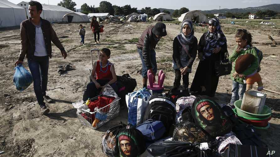 FILE - Syrian refugees wait with their belongings to leave a makeshift camp near the northern Greek village of Idomeni during a police operation at the Greek-Macedonian border, May 26, 2016.