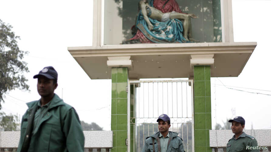 FILE - Members of the police stand guard in front of a replica of Pieta at Holy Rosary Church in Dhaka.
