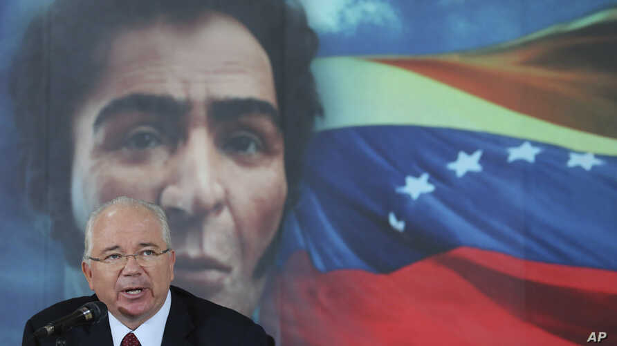 FILE - In this Oct. 10, 2014 file photo, Venezuela's then Foreign Minister Rafael Ramirez gives a press conference backdropped by an image of independence hero Simon Bolivar, in Caracas, Venezuela.