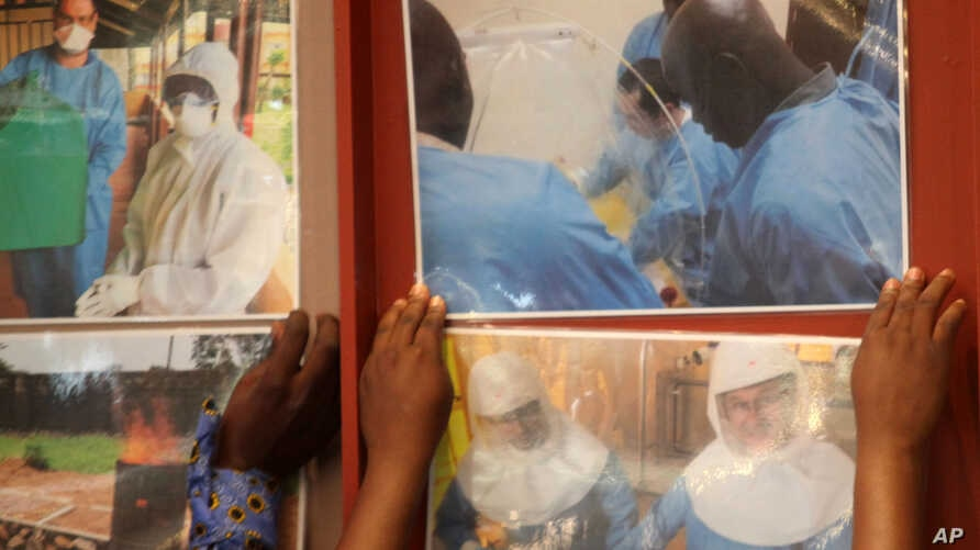 Delegates paste enlarged photos of health workers at work in affected west African countries prior to attending an Ebola preparedness conference in Johannesburg, Oct. 10, 2014.