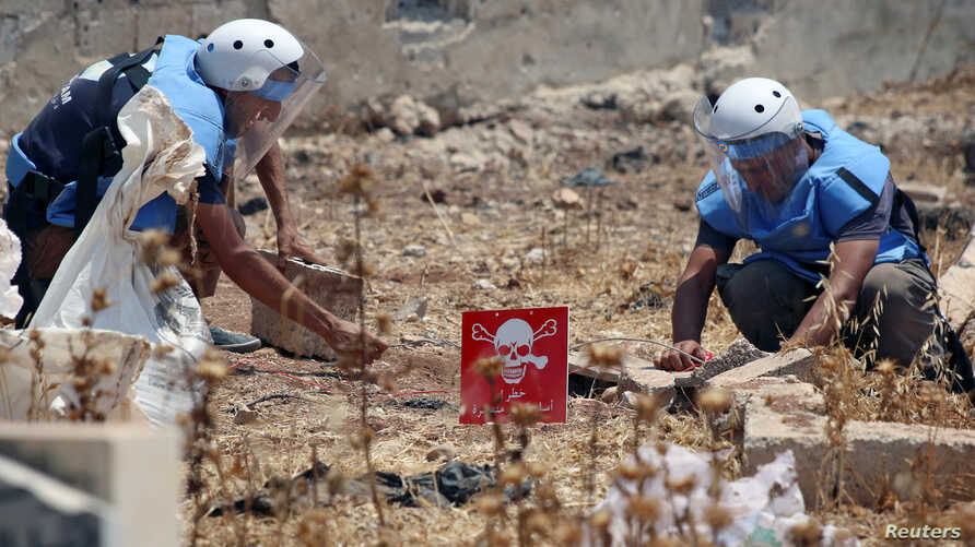 Civil defense members prepare to safely detonate cluster bombs in the rebel-held area in Deraa, Syria, July 26, 2017.