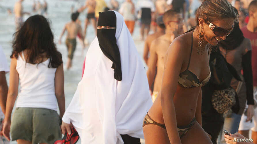 A woman wearing a bikini walks past a woman wearing a niqab on a beach in the Mediterranean city of Alexandria, about 220 km northwest of Cairo,Egypt, Aug. 7, 2009.