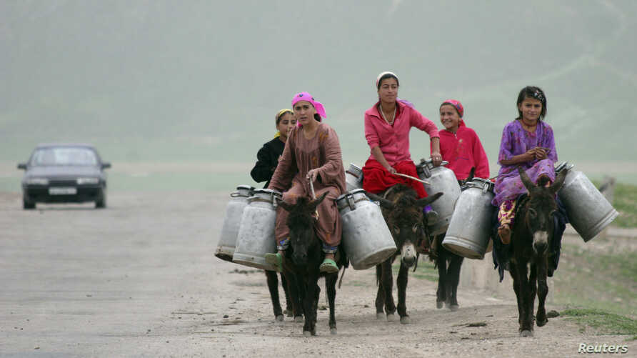 FILE - Women ride donkeys loaded with water canisters outside the Central Asian village of Gargara, 110 kilometers (68 miles) south of Dushanbe, Tajikistan, May 4, 2008.