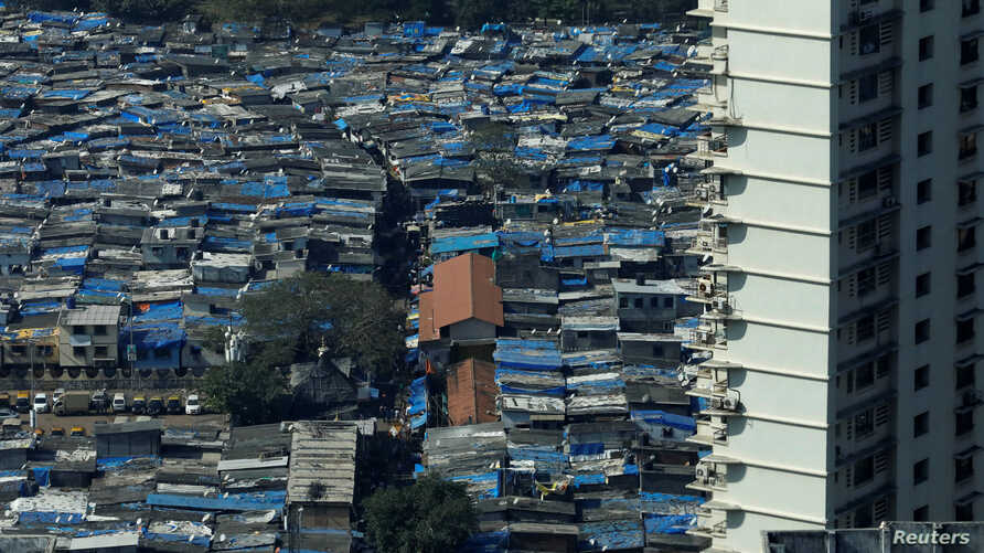 A high-rise residential building is seen next to a slum in Mumbai, India, Dec. 20, 2017.