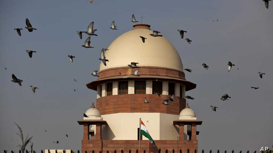 FILE - Pigeons fly past the dome of India's Supreme Court building in New Delhi, India.