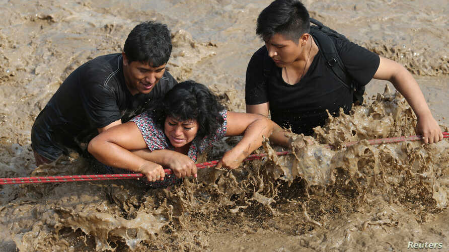 Rescuers help people cross a flooded street after a massive landslide and flood in the Huachipa district of Lima, Peru, March 17, 2017.