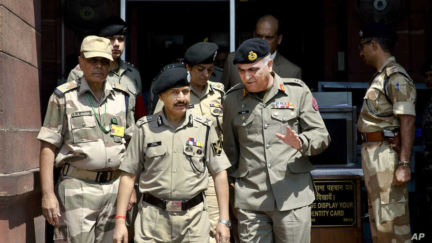Indian Border Security Force (BSF) Director General D.K. Pathak, center left, and Pakistani Rangers Director General (Punjab) Maj. Gen Umar Farooq Burki, center right, chat as they leave after their meeting with Indian Home Minister Rajnath Singh in